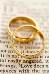 Two Wedding Rings Resting On A Bible Page